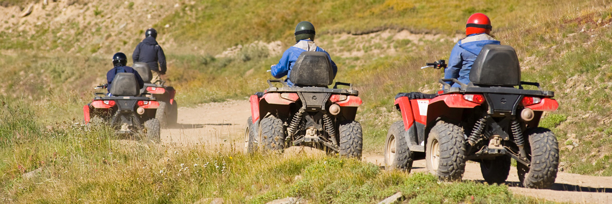 Four people riding ATVs on a trail