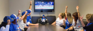 Roughley Insurance staff members cheering around a table while watching a Toronto Blue Jays game