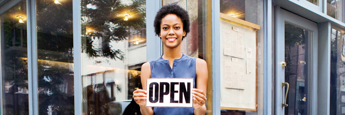 "A woman stnading outside her storefront holding a sign that says ""open"""