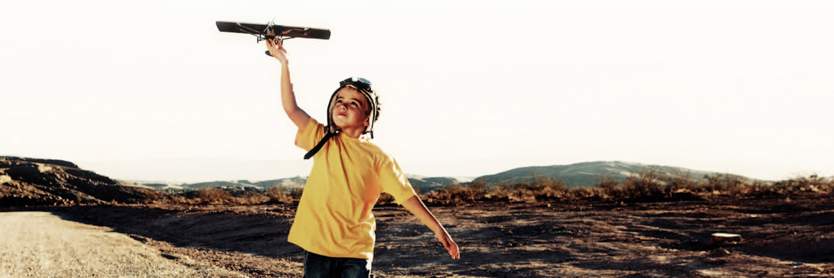 A young boy playing with a toy airplane
