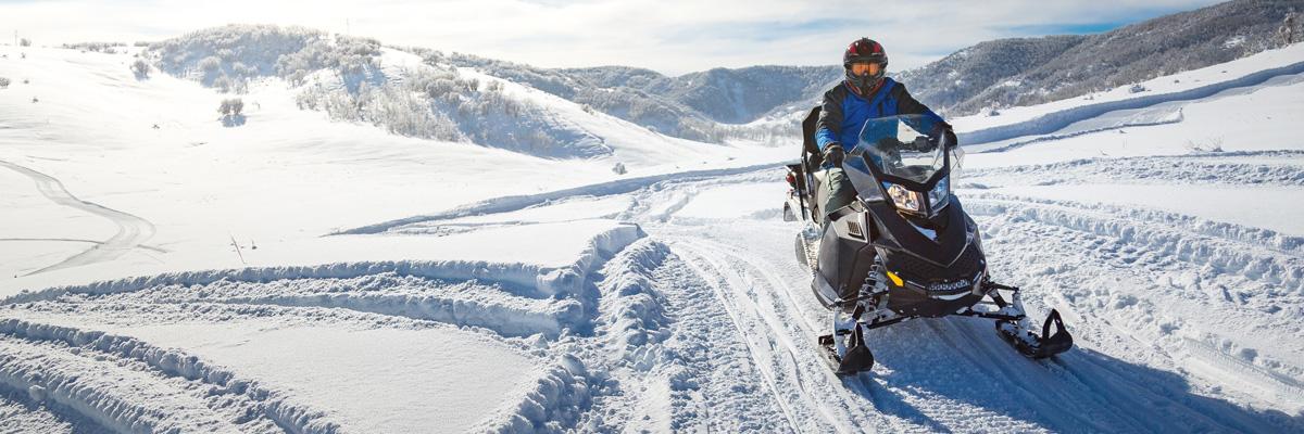 Person driving a snowmobile through a mountain trail